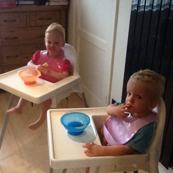 Smidge and Smudge sitting in their high chairs, eating