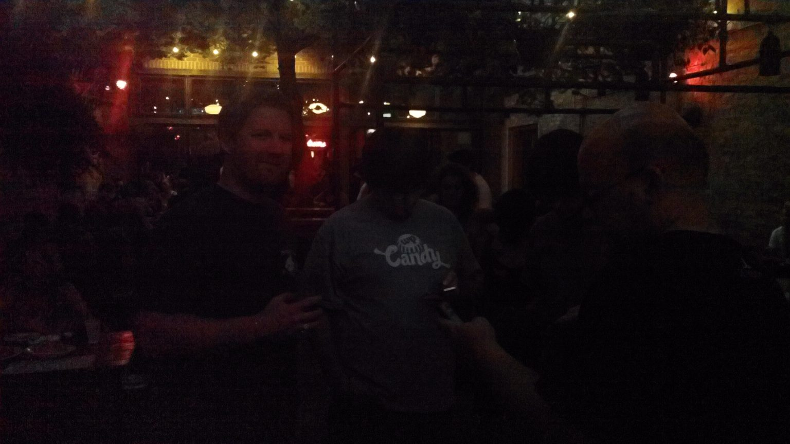 Dark shot of people standing around a beer garden looking at their phones
