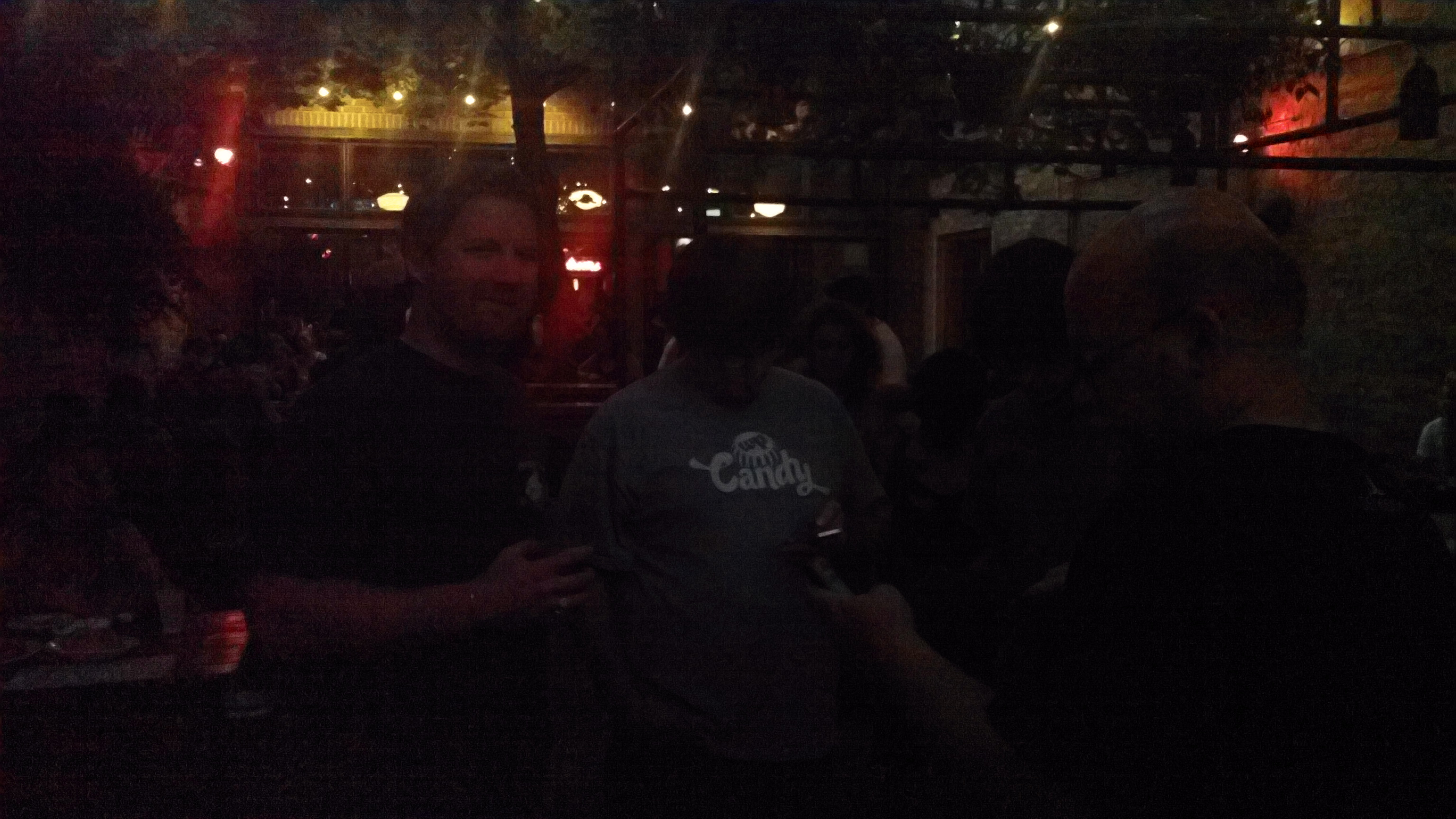 Dark shot of people standing around a beer garden looking at their phones