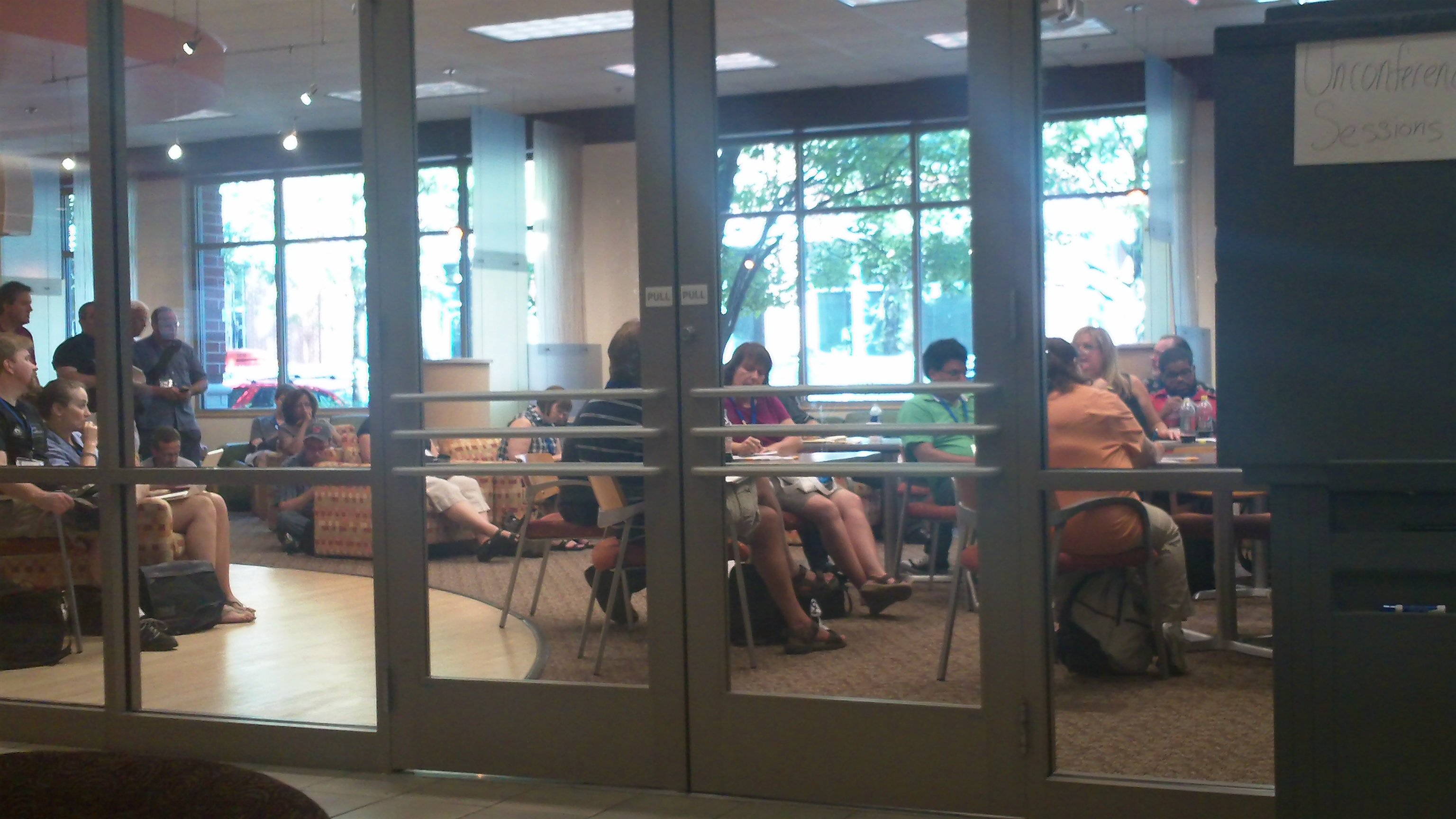 People sitting in a room behind glass doors