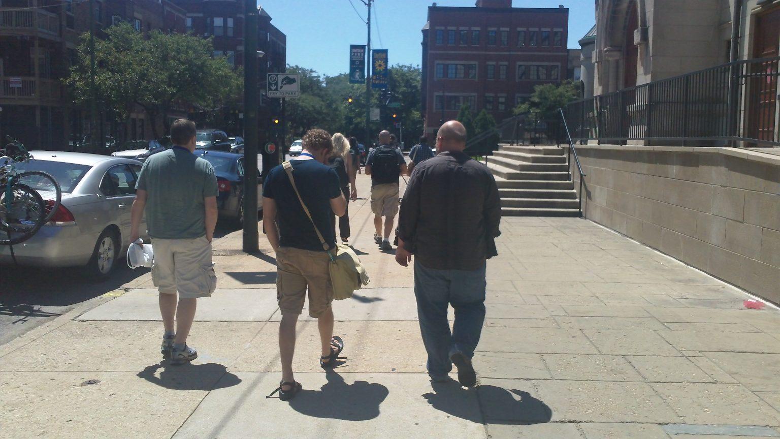 Three people walking away, down the road