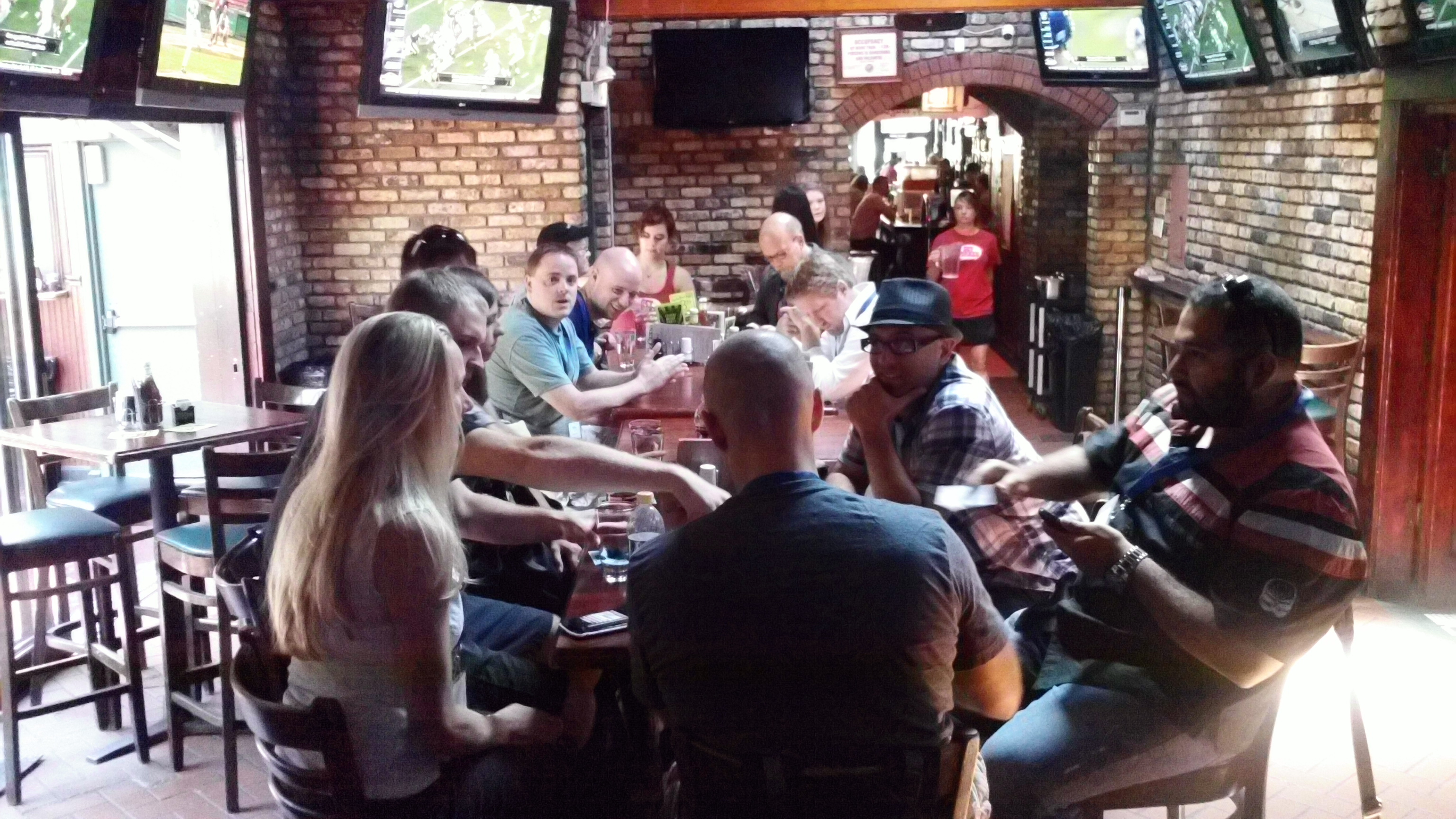 Photo of people sitting around a table awaiting lunch in a bar