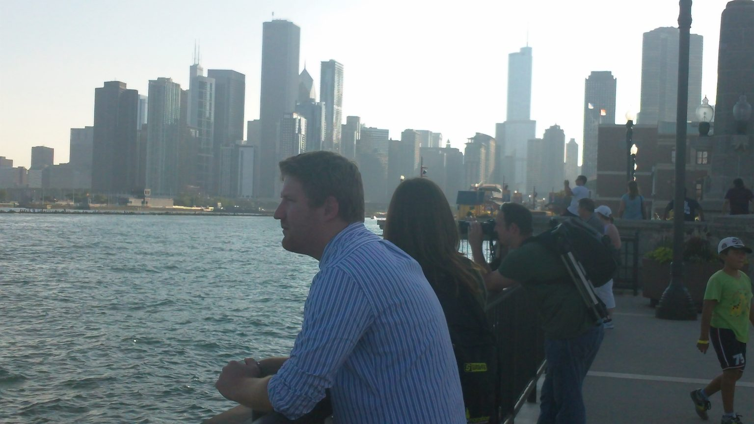 Jared and Sam in the foreground, with the harbour and city partially in shadow behind them