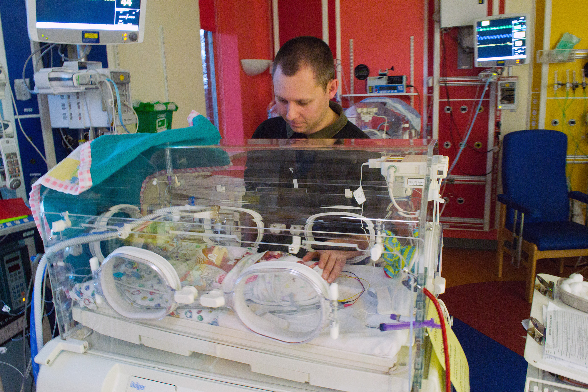 Small baby in incubator, with Daddy looking in